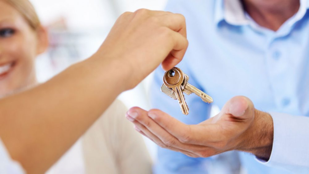 mortgage banker gives keys to homebuyer