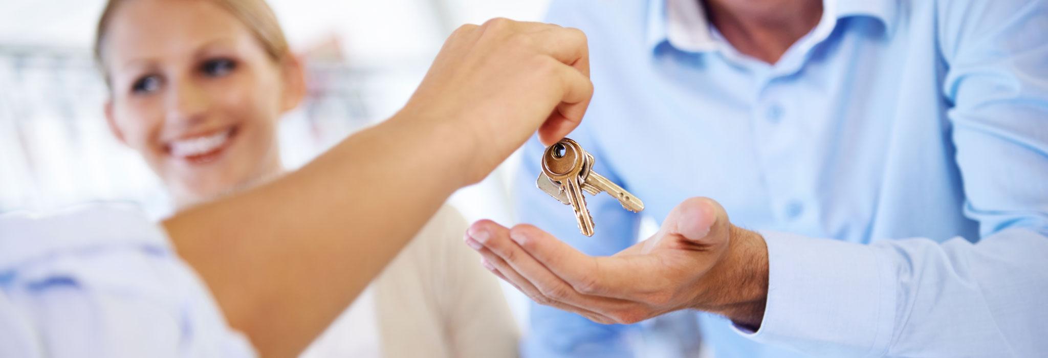 mortgage banker gives keys to homebuyer